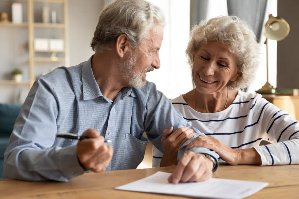 Older couple discuss agreement ready to sign contract