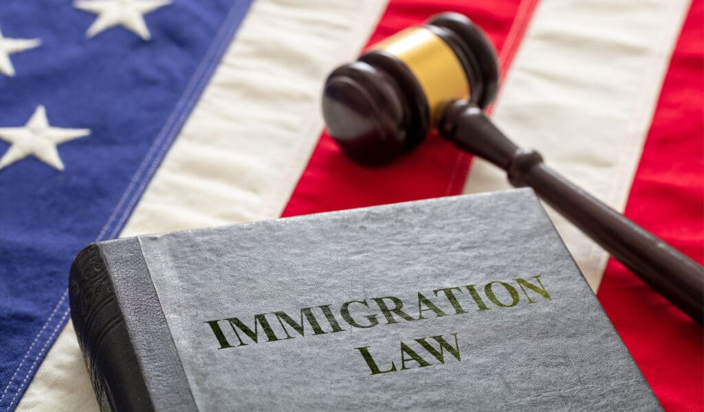 Immigration law text on black book and judge gavel on US of America flag background. Migration, emigration visa in USA concept